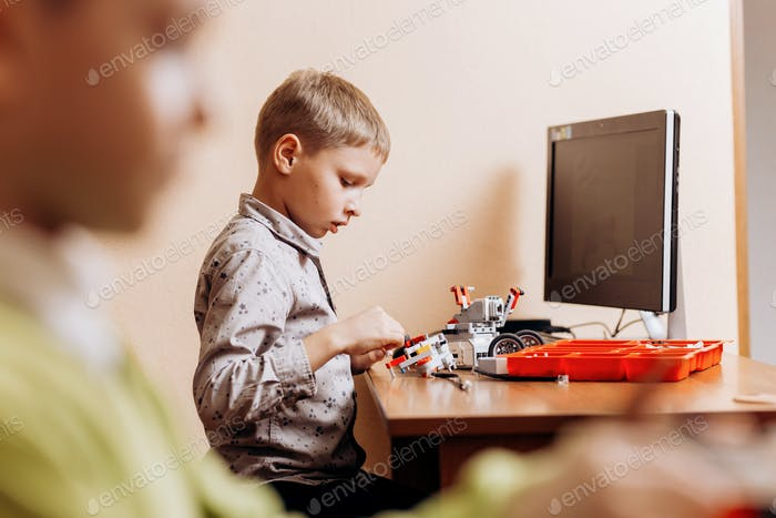 Diligent boy dressed in gray shirt makes a robot from the robotic constructor at the desk with