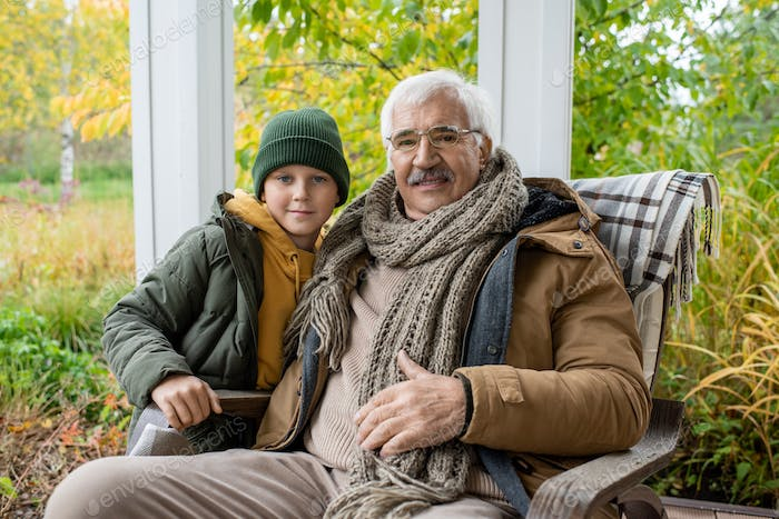 Cute schoolboy in beanie and warm jacket and his grandfather in rocking chair
