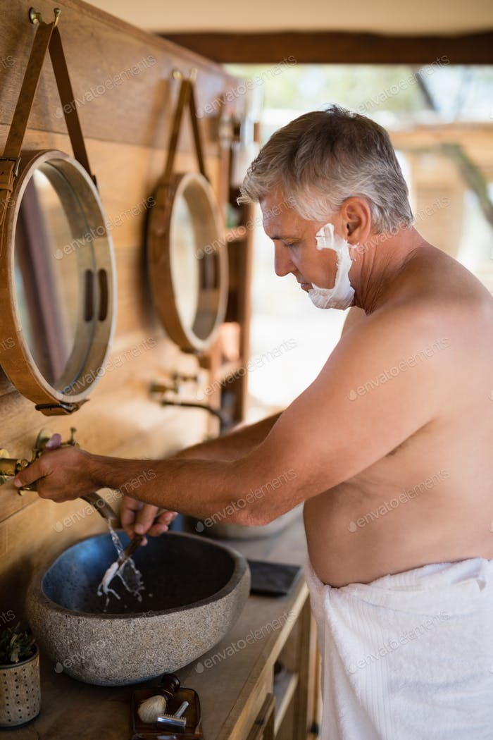 Man washing razor in cottage