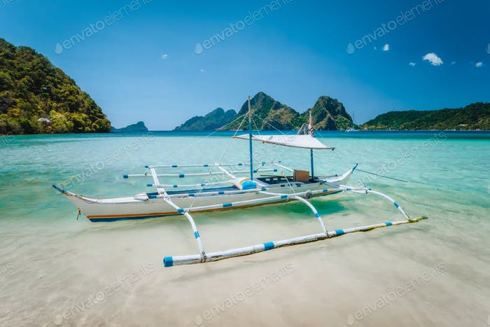 El Nido, Palawan, Philippines. Local tourist banca boat for island hopping trip. Beautiful mountains