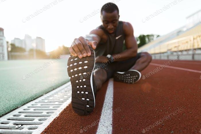 Young concentrated african male athlete stretching legs