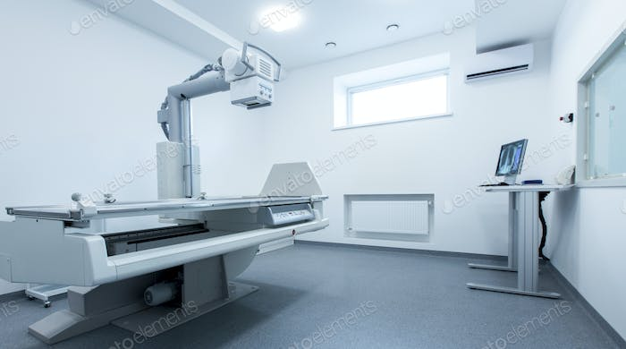 Clean and light X-ray room with chest on monitor