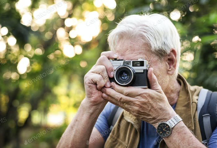 Senior trekker taking a photo with a film camera
