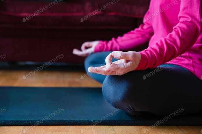 Hands close up of middle aged woman sitting in lotus position on yoga mat in her living room.