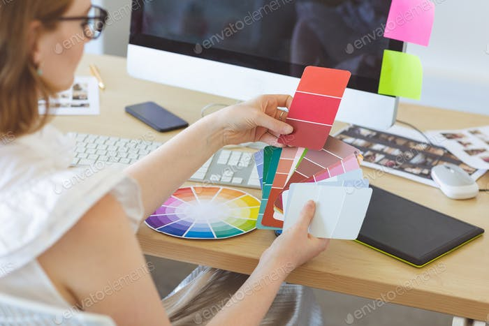 Young graphic designer checks the color with color swatch at desk in office