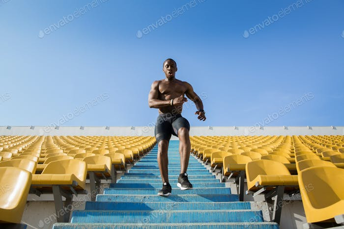 Young male athlete exercising by running downstairs