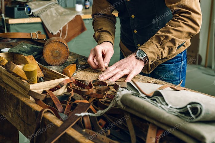 Midsection of man working at workbench in bag factory