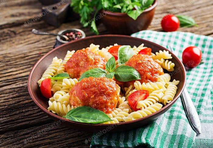Fusilli  pasta with meatballs in tomato sauce and basil in bowl. Italian cuisine.