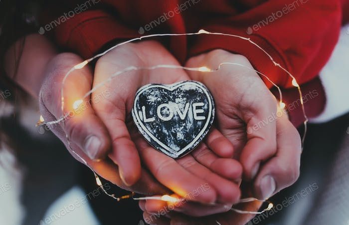 Hands holding stone heart with love text. Blurred background