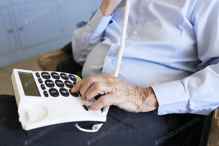Senior Man At Home Using Telephone With Over Sized Keys