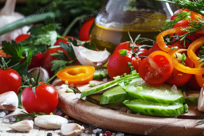 Cut fresh vegetables, spices and olive oil for a spring salad, healthy food