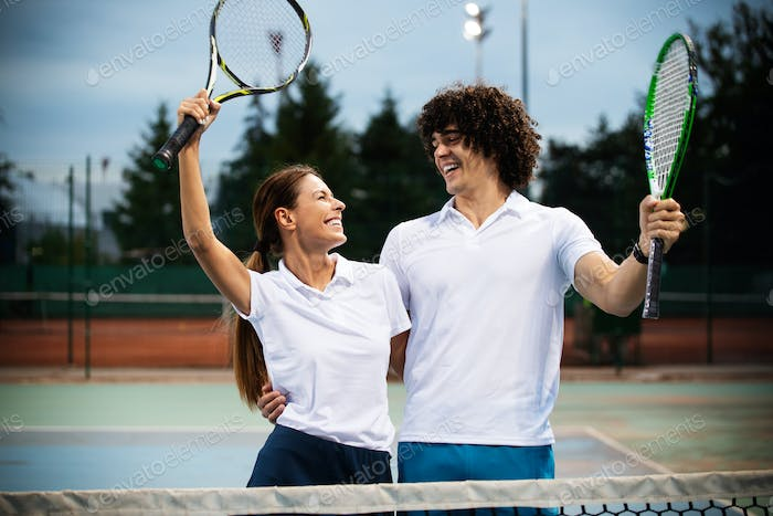 Fit happy poeple playing tennis together. Sport concept