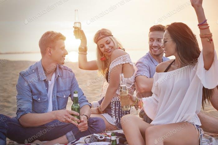 Four friends having fun at the beach party