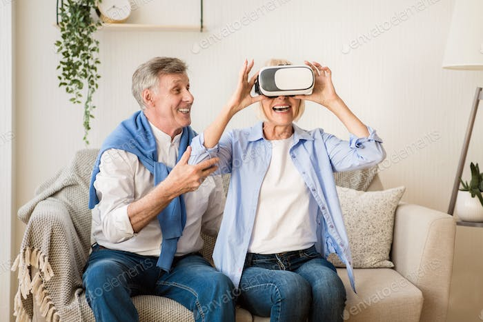 Mature woman testing VR glasses with husband