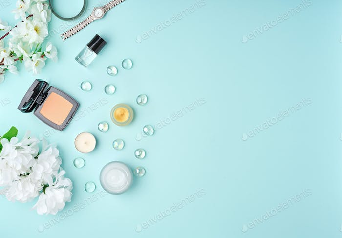 Flat lay woman accessories with cosmetic, facial cream, bag, flowers on pastel blue table.