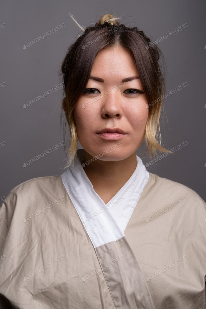 Young beautiful Kazakh woman against gray background