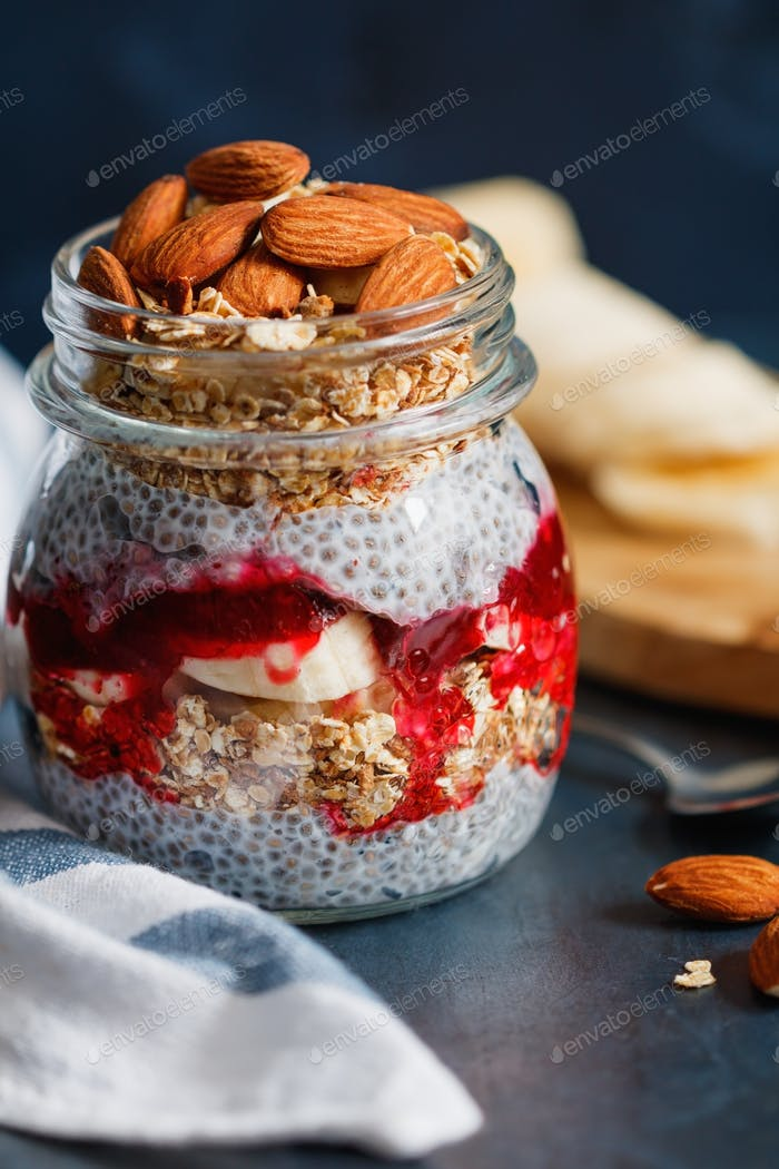 Organic chia pudding with granola, banana, jam and almonds. The concept of healthy food.