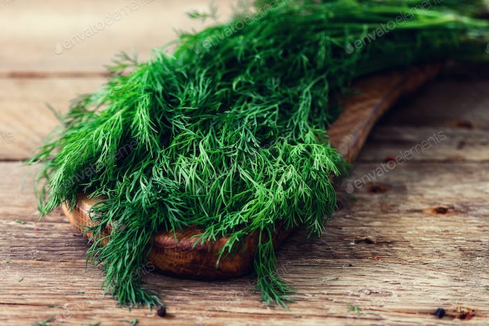 Bunch of fresh organic dill on wooden background with copyspace, rustic and vintage style, selective