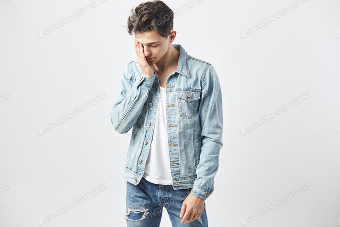 Sad dark-haired guy dressed in a white t-shirt, jeans and a denim jacket holds his hand on the face