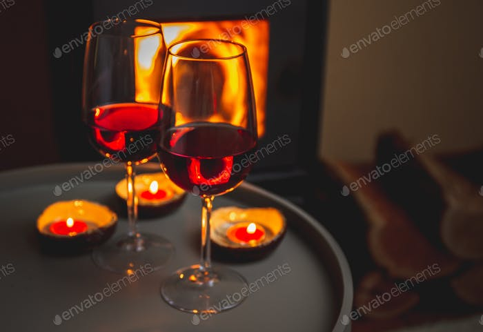 Two glasses of red wine front of fireplace. Romantic light