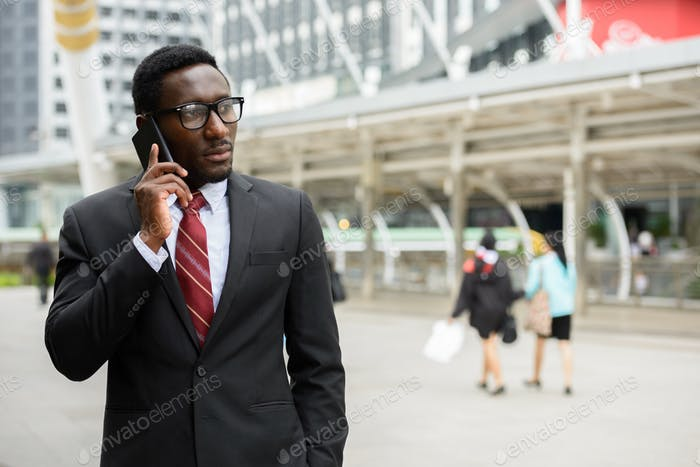 Young handsome African businessman talking on mobile phone in front of modern building at Bangkok