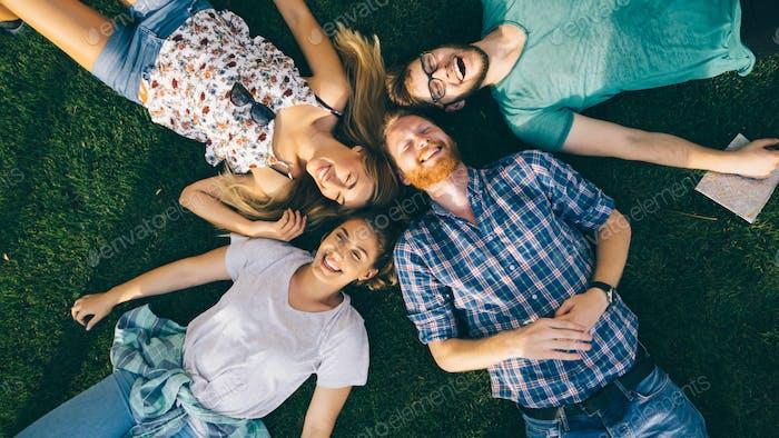 Glückliche freudige Schüler liegen im Gras