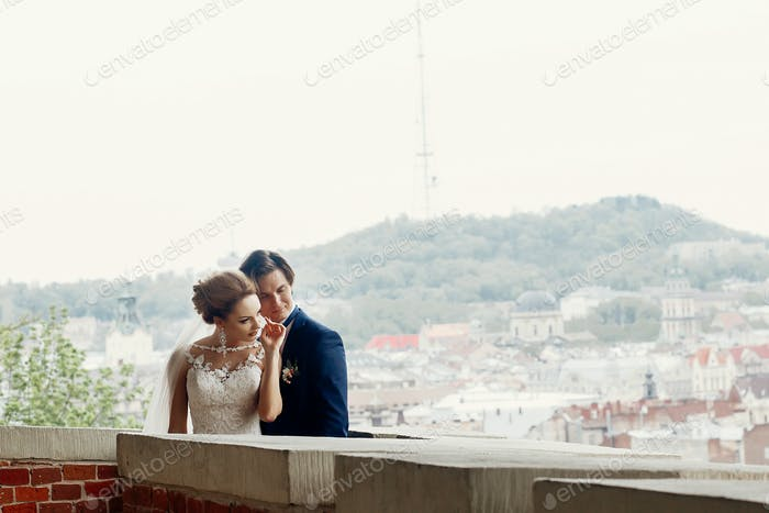 Happy newlywed couple on castle wall, cityscape and hill in the background