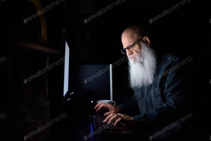 Stressed mature bald bearded man working overtime at home in the dark