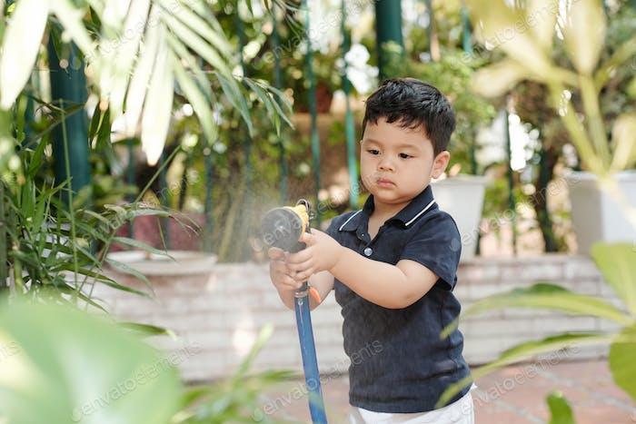 Kid enjoying watering flowers