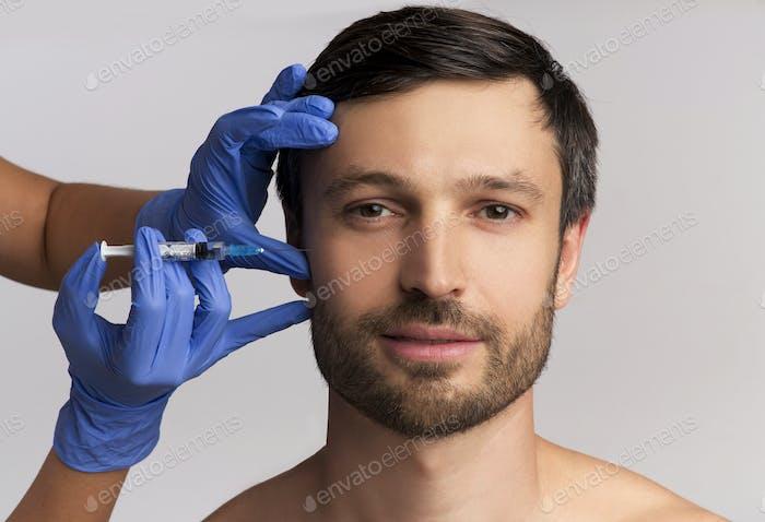 Porträt von Mann mittleren Alters Empfangen Falten-Entfernen Injektion, weißer Hintergrund
