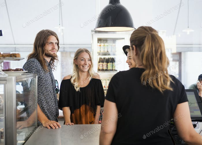 Friends talking with waitress at restaurant counter