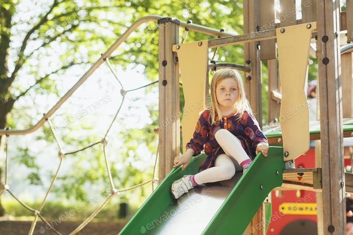 Cute girl sitting on slide at playground