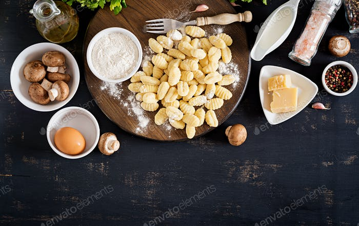Uncooked homemade Gnocchi with a mushroom cream sauce and parsley