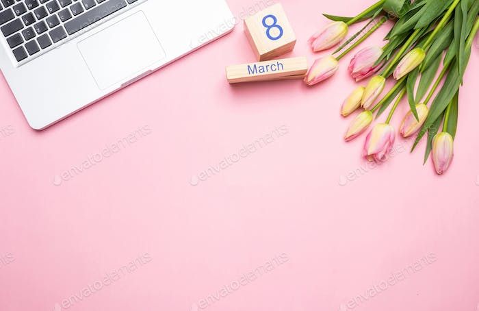 Pink tulips bouquet, date March 8th and laptop on pink background, top view, copy space