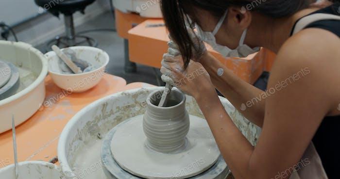 Woman make pottery wheel, shaping a clay pot