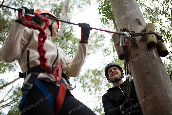 Hiker woman holding zip line in forest