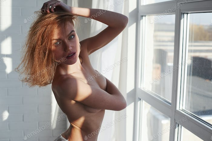Nice sexy look. Young red haired girl with bare chest stands near the window at daytime