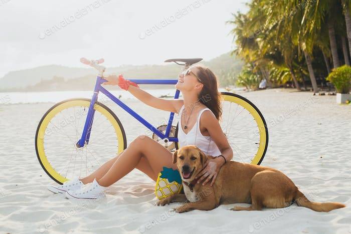 young beautiful woman sitting on sand on beach, holding vintage bicycle