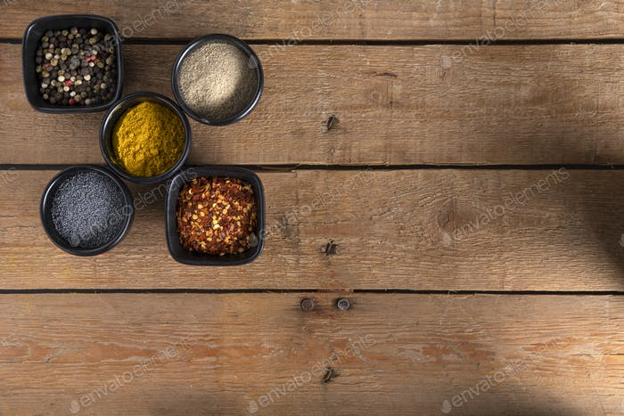 Different kind of Spices in bowls on the left side of a wooden table