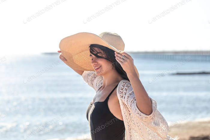 Beautiful woman in hat and bathing suit on the beach.