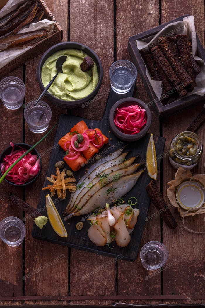 Assorted marinated fish on dark cutting board with vodka shots.