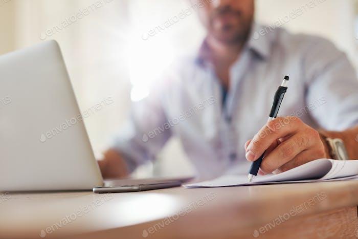 Young business man hands writing notes