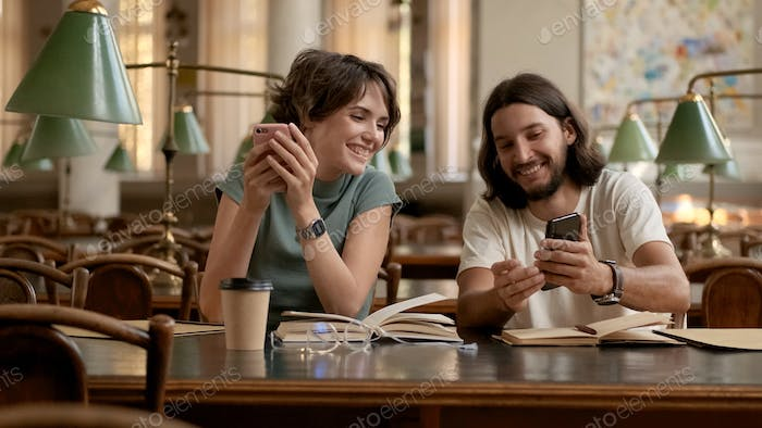 Attractive young students happily using smartphones while preparing for exams in library