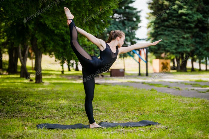 Young girl practicing yoga in nature in the woods on a background of green trees and grass. She