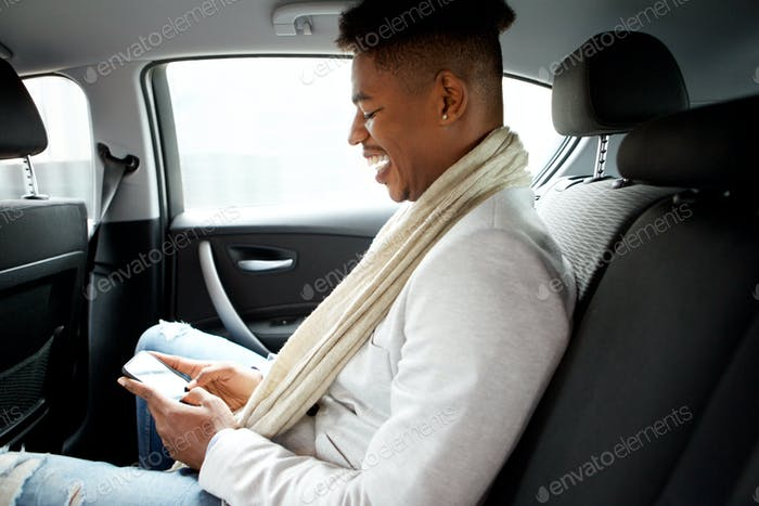 smiling young african american man looking at cellphone while in backseat of car