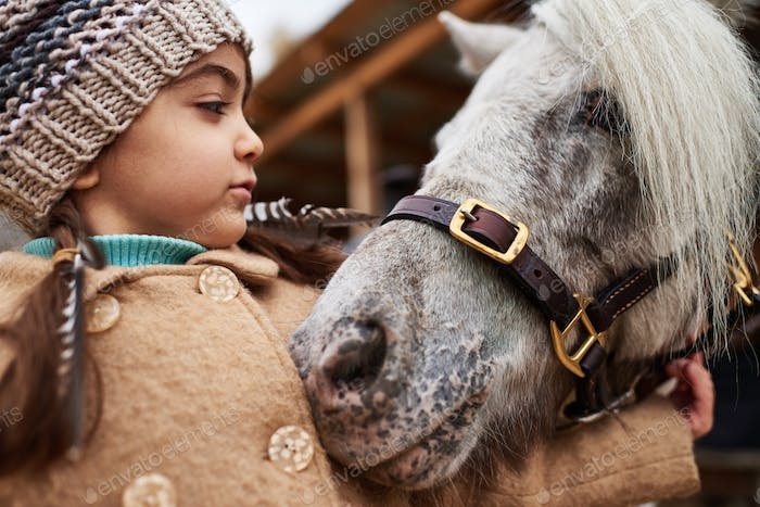 Pony Snuggling Up To Little Girl