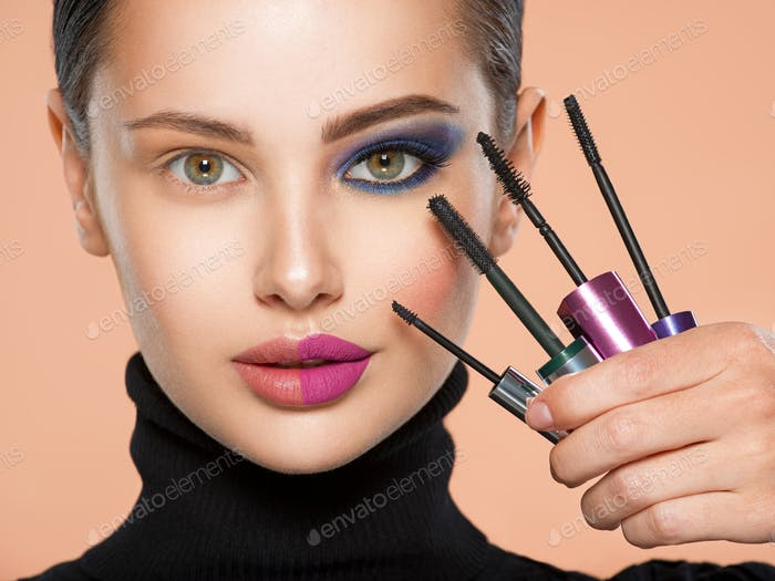 Closeup face of a beautiful white woman with  brushes for mascara.