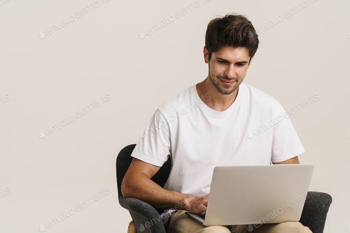 Porträt zufriedener Mann mit Laptop arbeiten, während auf Sessel sitzen