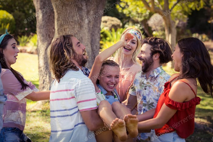 Group of friends lifting woman at campsite