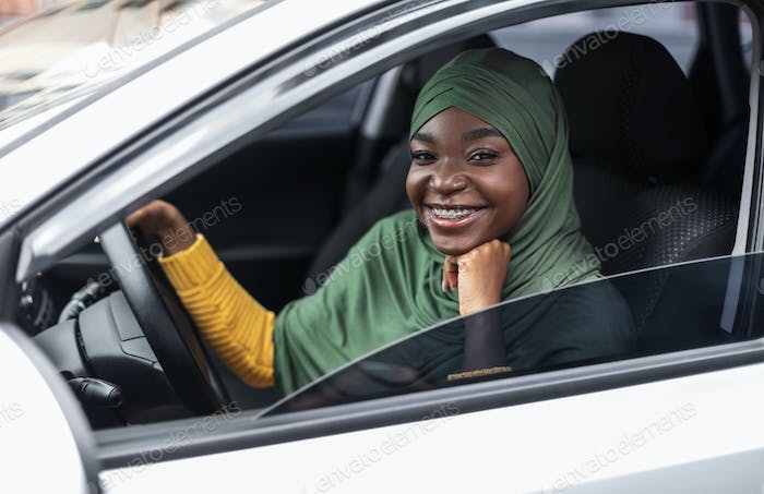 Happy Black Religious Woman In Hijab Posing Of Drivers Seat In Car